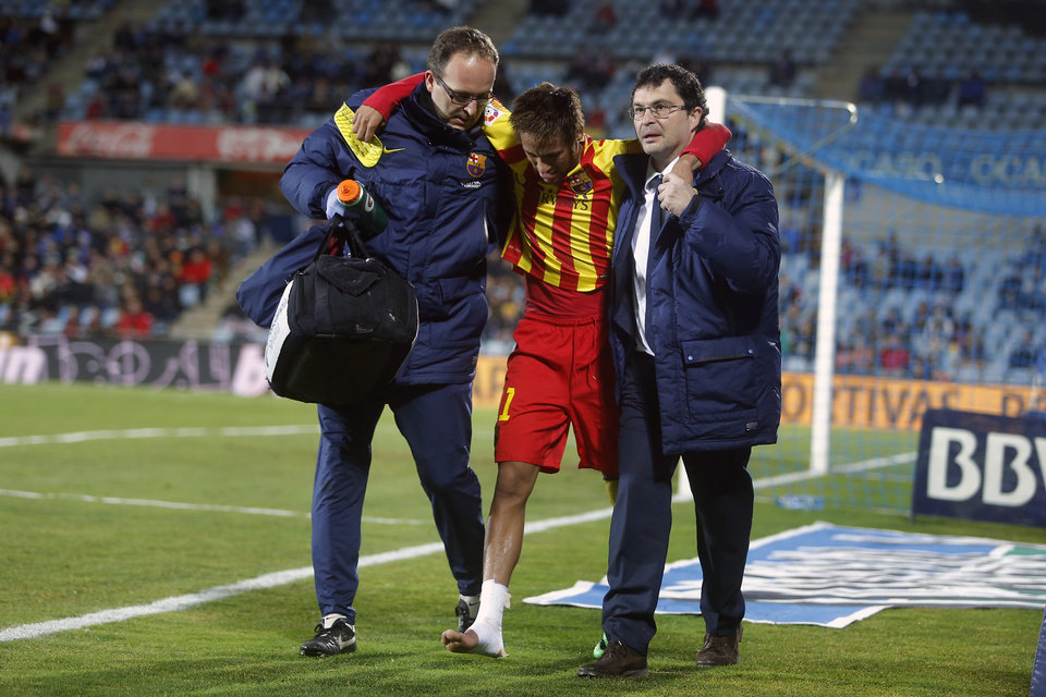 Photo - FC Barcelona's Neymar from Brazil, centre, leaves the field injured during a Spanish Copa del Rey match between FC Barcelona and Getafe at the Coliseum Alfonso Perez stadium in Madrid, Spain, Thursday, Jan. 16, 2014. (AP Photo/Andres Kudacki)