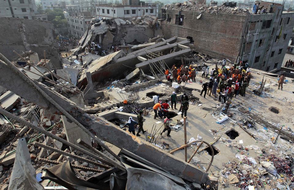 Photo - Bangladeshi rescuers work at the site of a building that collapsed Wednesday in Savar, near Dhaka, Bangladesh, Friday, April 26, 2013. More than two days after their factory collapsed on them, at least some garment workers were still alive in the corpse-littered debris Friday, pinned beneath tons of mangled metal and concrete. The death toll topped 300 on Friday and it remained unclear what the final grim number would be as some survivors are still being pulled from the rubble. (AP Photo/A.M. Ahad)