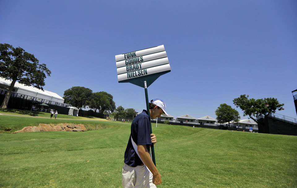Photo - Volunteer Samuel Jackson carries the name board as he walks to the 11th tee box during practice rounds for the U.S. Senior Open golf tournament at Oak Tree National in Edmond, Okla. on Monday, July 7, 2014. Photo by Chris Landsberger, The Oklahoman
