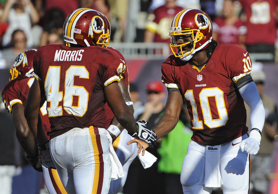 Washington Redskins quarterback Robert Griffin III (10) shakes hands with running back Alfred Morris (46) after Griffin III scored a touchdown against the Tampa Bay Buccaneers during the second quarter of an NFL football game Sunday, Sept. 30, 2012, in Tampa, Fla. (AP Photo/Brian Blanco)