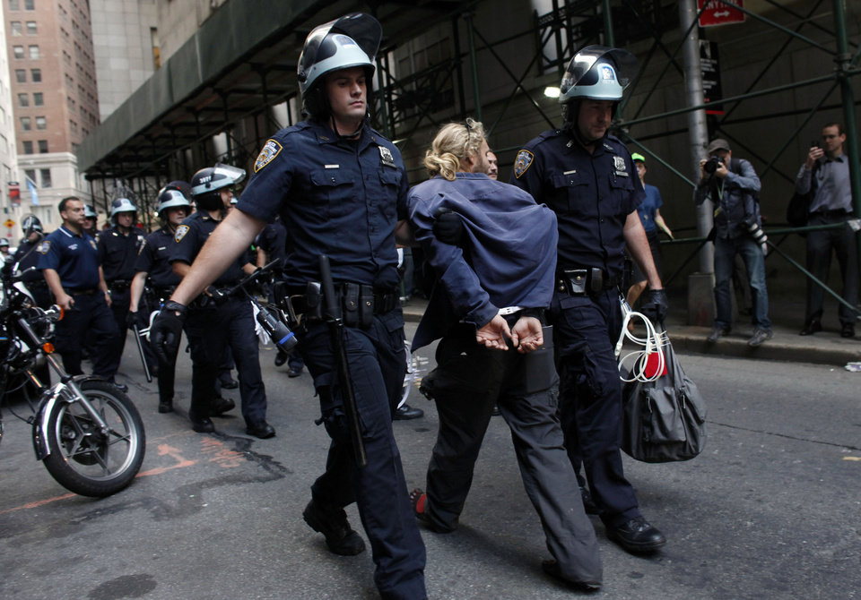 Photo -   Police officers lead a man away during an Occupy Wall Street march, Monday, Sept. 17, 2012, in New York. A handful of Occupy Wall Street protestors were arrested during a march on the New York Stock Exchange on the anniversary of the grass-roots movement. (AP Photo/Jason DeCrow)