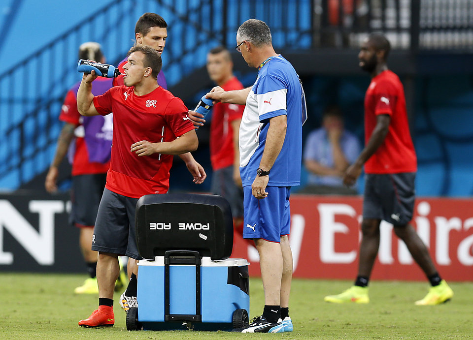 Photo - Switzerland's Xherdan Shaqiri, left, refreshes  during a training session at the Arena da Amazonia in Manaus, Brazil, Tuesday, June 24, 2014, one day before the group E match between Honduras and Switzerland of the 2014 soccer World Cup. (AP Photo/Frank Augstein)