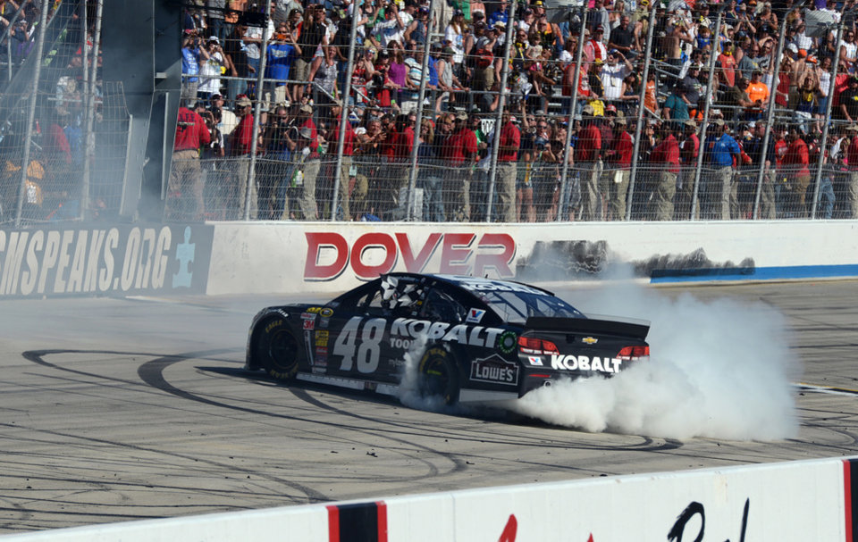Photo - Jimmie Johnson does a burn-out after winning the NASCAR Sprint Cup series auto race at Dover International Speedway, Sunday, June 1, 2014, in Dover, Del. (AP Photo/Molly Riley)