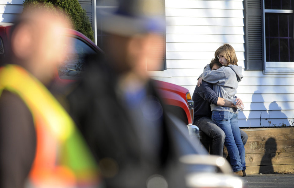 Photo - People embrace at a firehouse staging area for family around near the scene of a shooting at the Sandy Hook Elementary School in Newtown, Conn. where authorities say a gunman opened fire, leaving 27 people dead, including 20 children, Friday, Dec. 14, 2012. (AP Photo/Jessica Hill) ORG XMIT: CTJH109