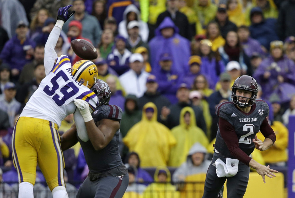 Photo - LSU defensive end Jermauria Rasco (59) bats down a pass by Texas A&M quarterback Johnny Manziel (2) in the first half of an NCAA college football game in Baton Rouge, La., Saturday, Nov. 23, 2013. (AP Photo/Gerald Herbert)