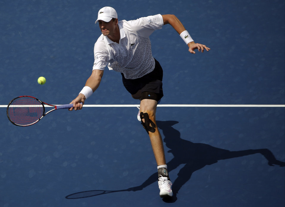 Photo - John Isner, of the United States, comes to the net to return a shot against Marcos Giron, of the United States, during the first round of the 2014 U.S. Open tennis tournament, Tuesday, Aug. 26, 2014, in New York. (AP Photo/Kathy Willens)