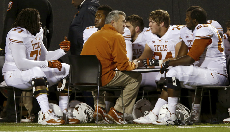 Photo - Texas offensive coordinator Joe Wickline works with the offense on the sideline during the college football game between the Oklahoma State University Cowboys (OSU) the University of Texas Longhorns (UT) at Boone Pickens Staduim in Stillwater, Okla. on Saturday, Nov. 15, 2014.  Photo by Chris Landsberger, The Oklahoman