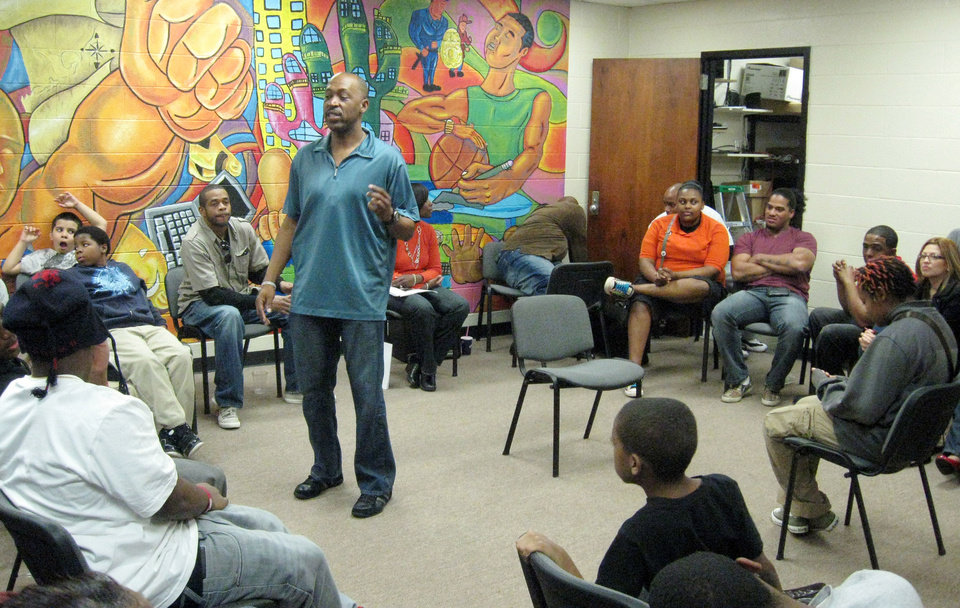Photo - Sgt. Wayland Cubit discusses conflict resolution with a group of youth during the weekly FACT meeting at the Hathaway Center on the city's southeast side. Devante Clark helped paint the mural in the background.  MATT DINGER - MATT DINGER