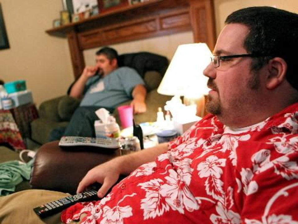 Alex Gates (right) and guests watch television during a Lost party at the home of Alex and Amber Gates in Moore, Okla., on Sunday, May 23, 2010. Photo by  John  Clanton