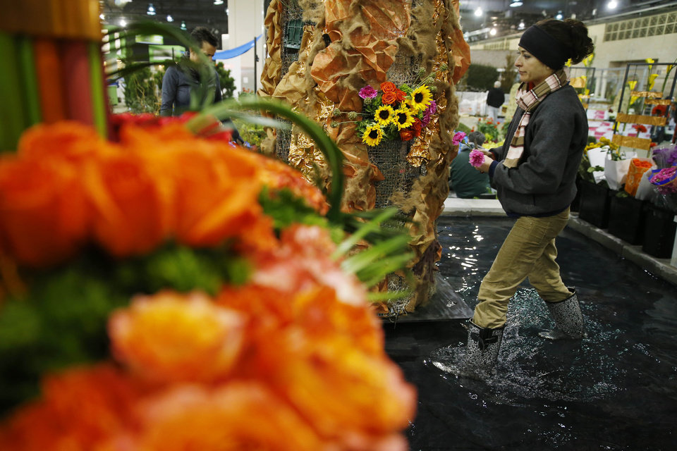 Photo - Jennifer Stewart with Flowers by David places flowers in preparation for the annual Philadelphia Flower Show at the Pennsylvania Convention Center, Thursday, Feb. 27, 2014, in Philadelphia. The nation's largest flower show will feature huge horticultural displays inspired by the work of artists such as Matisse, Mondrian, Calder and Kandinsky.