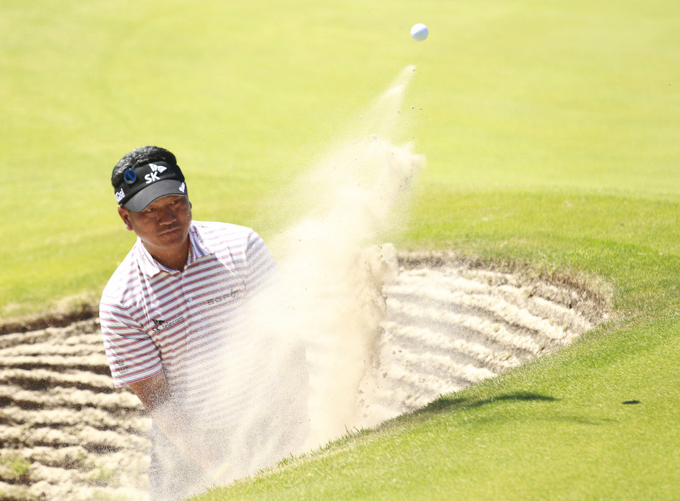 Photo - KJ Choi of Korea plays out of a bunker on the 15th hole during a practice round ahead of the British Open Golf championship at the Royal Liverpool golf club, Hoylake, England, Tuesday July 15, 2014. The British Open Golf championship starts Thursday July 17. (AP Photo/Peter Mossison)