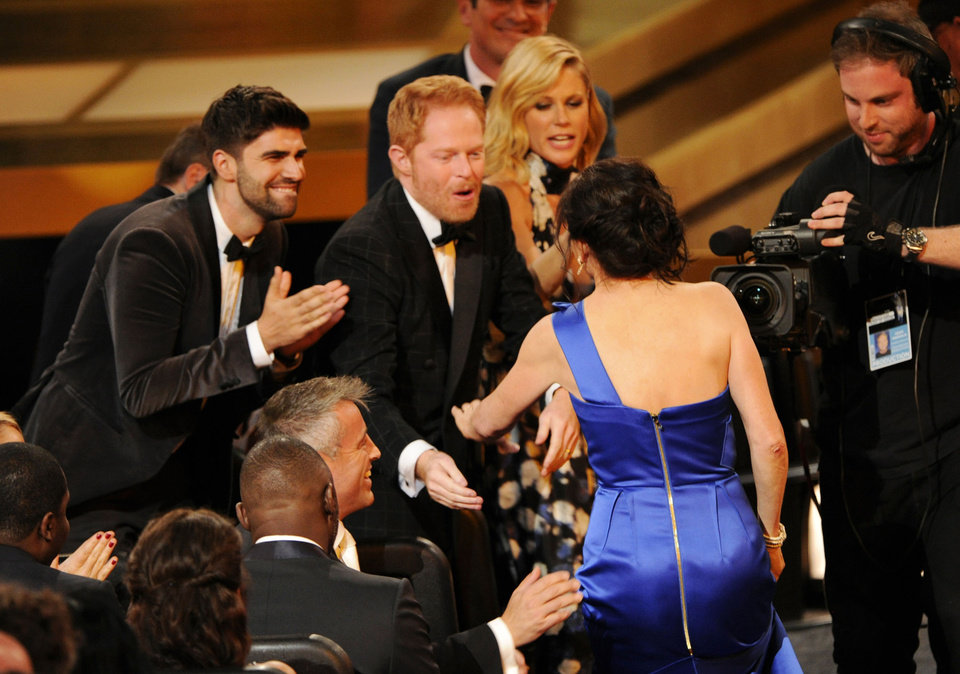 "Photo - Gail Mancuso accepts the award for outstanding directing for a comedy series for her work on ""Modern Family"" at the 66th Annual Primetime Emmy Awards at the Nokia Theatre L.A. Live on Monday, Aug. 25, 2014, in Los Angeles. Looking on from left are Justin Mikita, Jesse Tyler Ferguson and Julie Bowen. (Photo by Chris Pizzello/Invision/AP)"