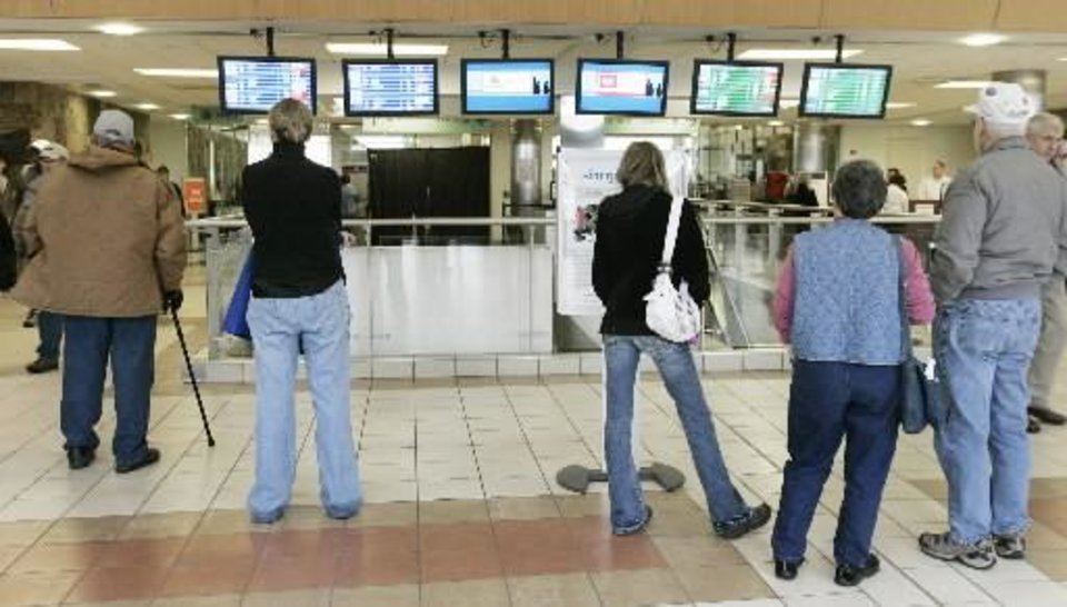 Photo - Will Rogers World Airport Arrival and Departure flights are shown as onlookers watch for cancelled or delayed flights by the icy weather Sunday, Dec. 9, 2007 in Oklahoma City,OK. BY JACONNA AGUIRRE