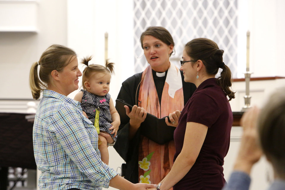 Photo - Same-sex marriages.  Megan Sibbett and Annemarie Mulkey say their marriage vows with daughter, Olive, and Rev. Lori Walke at Mayflower Congregational Church, 3901 NW 63, Monday, October 6, 2014. Photo by David McDaniel