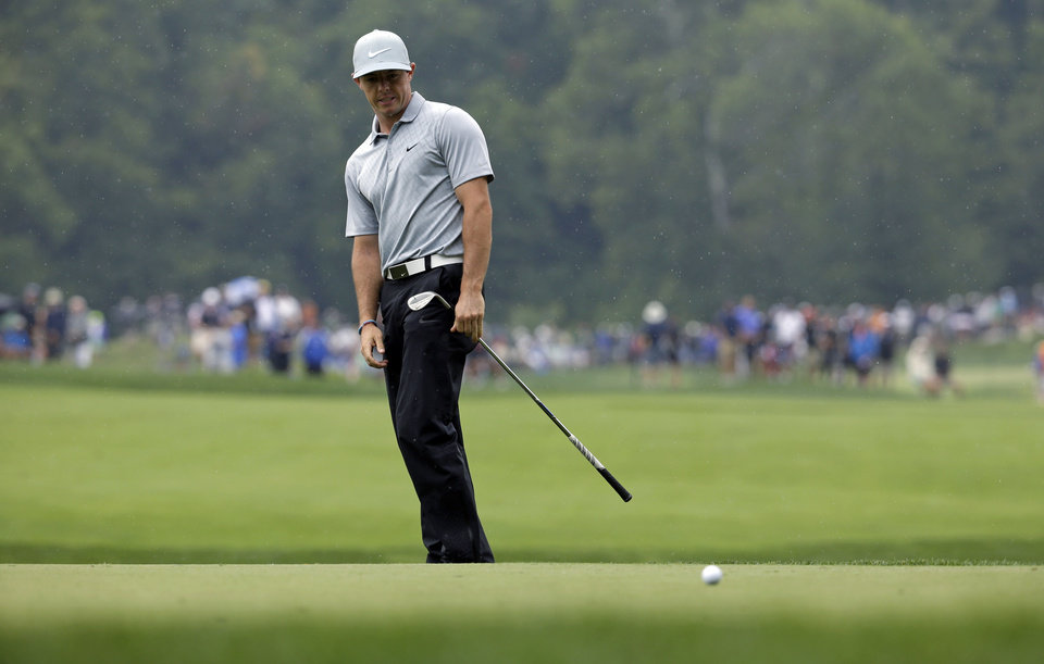 Photo - Rory McIlroy, of Northern Ireland, reacts after his chip to the fourth green during the second round of the PGA Championship golf tournament at Valhalla Golf Club on Friday, Aug. 8, 2014, in Louisville, Ky. (AP Photo/John Locher)