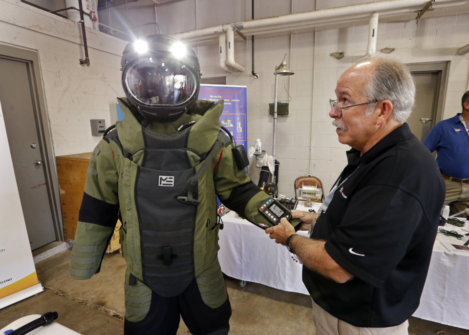 Photo -  A bomb disposal suit and helmet are shown by Johnnie Walden at a vendors' display at the International Association of Bomb Technicians and Investigators regional conference. [PHOTO BY STEVE SISNEY, THE OKLAHOMAN]