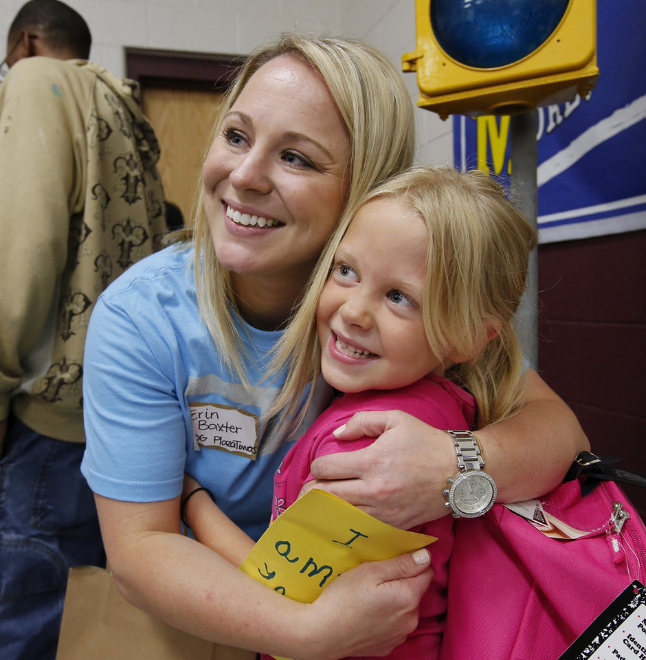 Kindergarten teacher Erin Baxter shares hugs with Ashlyn Smith, 6, one of her students. her students. There was lots of hugging and plenty of joy at Eastlake Elementary School on SW 134, when Eastlake School hosted a reunion of students, parents, teachers and families from Plaza Towers Elementary School on Thursday, May 23, 2013. Seven students died at Plaza Towers School in Monday\'s EF-5 tornado, which also destroyed the school. Photo by Jim Beckel, The Oklahoman.