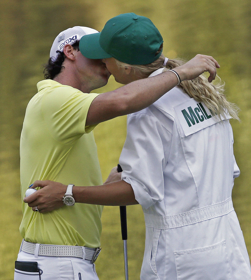 Photo - Rory McIlroy, of Northern Ireland, kisses his caddy and girlfriend tennis player Caroline Wozniacki following the par three competition before the Masters golf tournament Wednesday, April 10, 2013, in Augusta, Ga. (AP Photo/David J. Phillip)