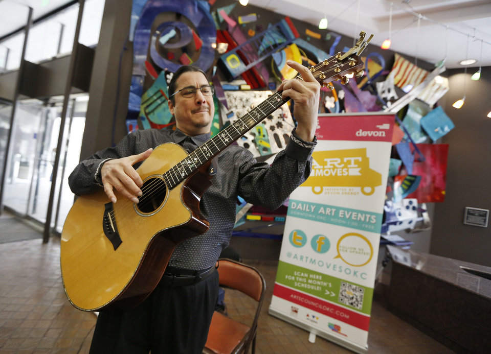 Photo - Acoustic Guitarist Edgar Cruz preforms in the Lobby of the Oklahoma Tower during a Art Moves concert in Oklahoma City, Friday February 07, 2014. Art Moves moves is sponsored by Devon Energy and provides free arts events in downtown area each work day from Noon-1:00. Photo By Steve Gooch, The Oklahoman
