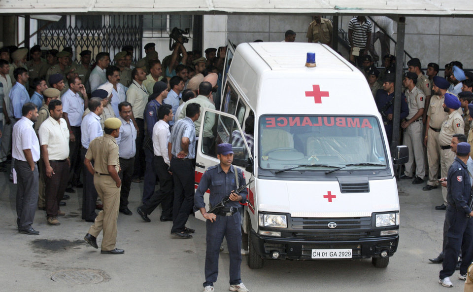 Photo - Security personnel stand guard as the body of a Pakistani prisoner Sanaullah Ranjay is carried into an ambulance outside a hospital in Chandigarh, India, Thursday, May 9, 2013. Ranjay, serving a life sentence in India, died Thursday from a beating that occurred a day after a convicted Indian spy was killed inside a Pakistani prison, an official said. The rival nations both have accused the other of not doing enough to protect prisoners. Ranjay was jailed in 1999 and was sentenced to life in prison in 2009 for being a Pakistani militant operating in Indian Kashmir. (AP Photo/Kapil Sethi)