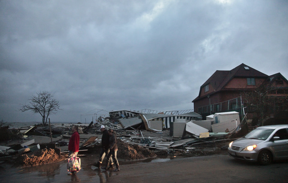 Photo - People walk through the houses destroyed in the aftermath of yesterday's storm surge from superstorm Sandy, Tuesday, Oct. 30, 2012, in Coney Island's Sea Gate community in New York. (AP Photo/Bebeto Matthews) ORG XMIT: NYBM118