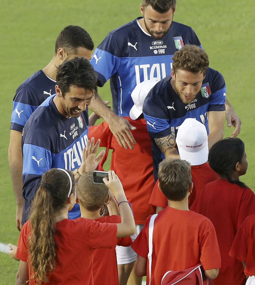 Photo - Italy players, from left, Gianluigi Buffon,  Leonardo Bonucci, Andrea Barzagli and Claudio Marchisio talk with children prior a training session of the Italian national soccer team in Natal, Brazil, Saturday, June 21, 2014. Italy play in group D of the 2014 soccer World Cup. (AP Photo/Antonio Calanni)