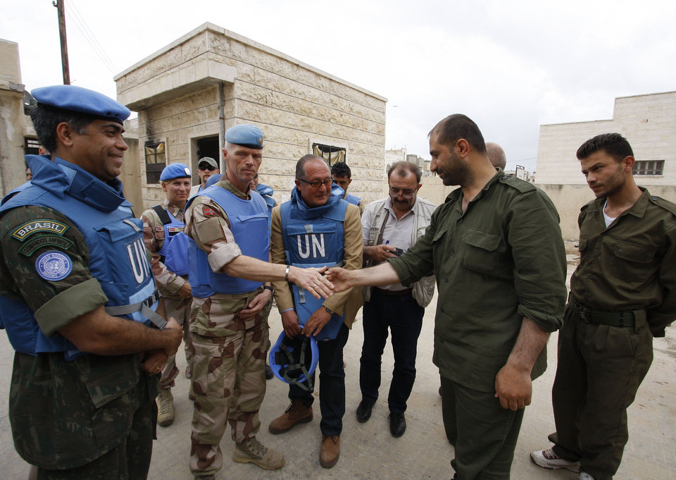 Photo -   In this picture taken during a UN observer-organized tour, the head of the advance team of UN observers, Maj. Gen. Robert Mood, center left, shakes hands with a Syrian security officer during their visit to Hama city, central Syria, on Thursday, May 3, 2012. Syrian security forces stormed dorms at a northwestern university to break up anti-government protests there, killing at least four students and wounding several others with tear gas and live ammunition, activists and opposition groups said Thursday. (AP Photo/Muzaffar Salman)