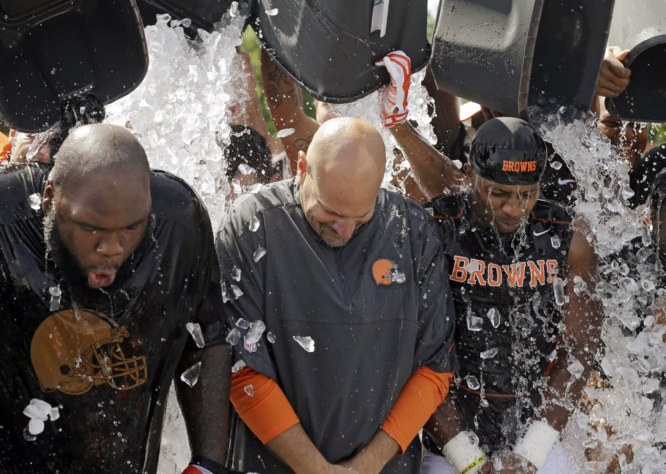 Photo - Cleveland Browns nose tackle Phil Taylor, left, head coach Mike Pettine, center, and cornerback Justin Gilbert get ice dumped over them after practice at NFL football training camp in Berea, Ohio Friday, Aug. 15, 2014. The Browns were challenged by the Baltimore Ravens to take the ALS Ice Bucket Challenge, to raise awareness about amyotrophic lateral sclerosis, also known as Lou GehrigÂ's Disease. (AP Photo/Mark Duncan)