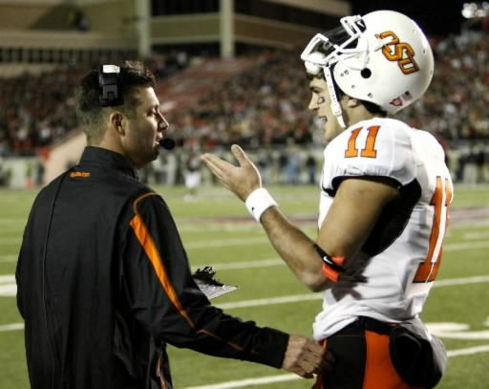 Photo - Head coach  Mike  Gundy talks with quarterback Zac Robinson during the second half of the college football game between the Oklahoma State University Cowboys (OSU) and the Texas Tech Red Raiders at Jones AT&T Stadium on Saturday, Nov. 8, 2008, in Lubbock, Tex. Texas Tech won 56-20. By Steve Sisney/The Oklahoman