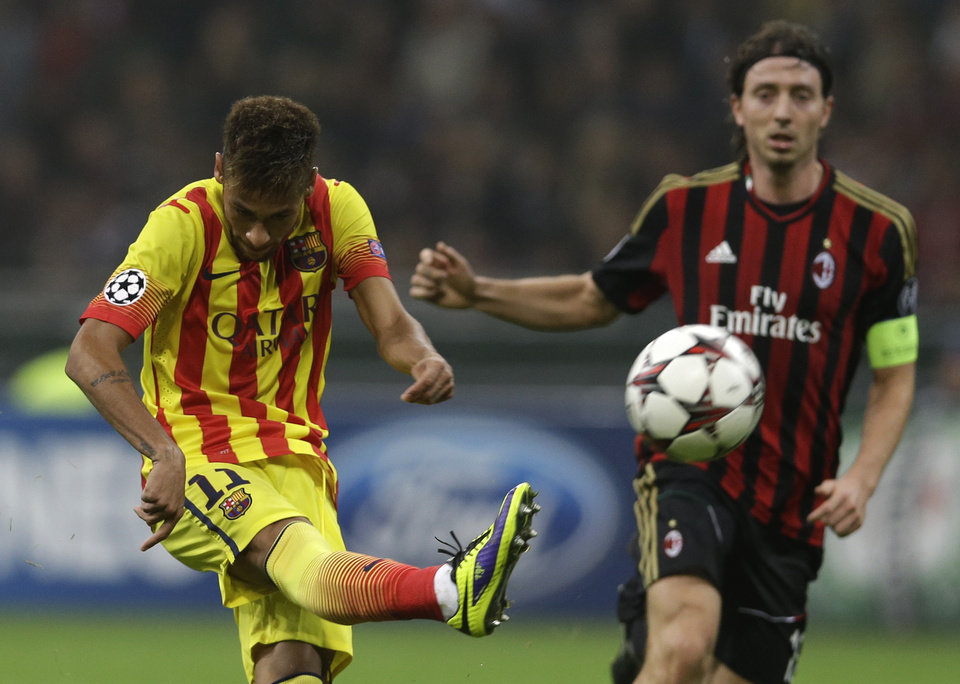 Photo - Barcelona's Neymar in action with AC Milan's Riccardo Montolivo during a Champions League, Group H, soccer match between AC Milan and Barcelona at the San Siro stadium, in Milan, Italy, Tuesday, Oct. 22, 2013.  (AP Photo/Luca Bruno)