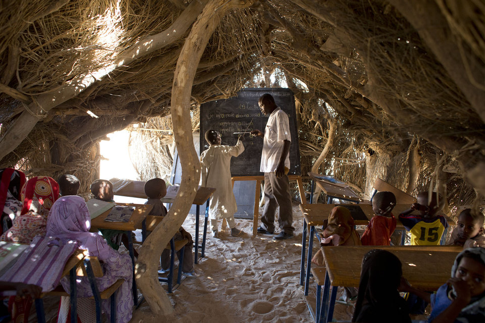 In this Nov. 2, 2012 photo, teacher Djobelsou Guidigui Eloi works with a student at the blackboard in Louri village's school hut in the Mao region of Chad. Many of the children, unable to read, attempted to pass the lesson by memorizing the sounds and their order on the blackboard. In 2011, 78 boys and girls enrolled in the equivalent of first grade in Chad's school system. Of those children, 42 failed the test to graduate into the next grade, a percentage that almost exactly mirrors the number of children stunted in the county. (AP Photo/Rebecca Blackwell) ORG XMIT: NY874