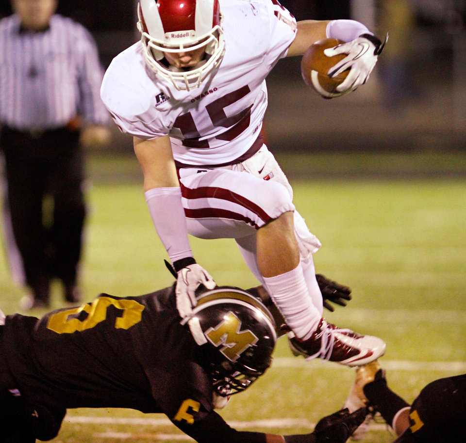 Photo - Owasso halfback Jake Burd leaps to escape the grasp of Bomber defensive back Antonio Martin on this 2nd quarter carry during  Class 6A playoff game between Midwest City Bombers and the Owasso Rams at Jim Darnell Stadium in Midwest City, Friday night, Nov. 18, 2011.  Photo by Jim Beckel, The Oklahoman