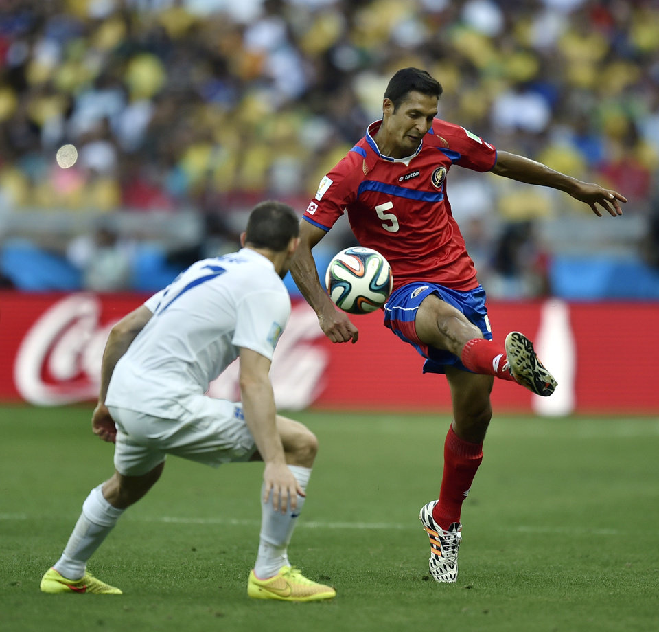 Photo - Costa Rica's Celso Borges, right, controls the ball past England's Jack Wilshere during the group D World Cup soccer match between Costa Rica and England at the Mineirao Stadium in Belo Horizonte, Brazil, Tuesday, June 24, 2014. (AP Photo/Martin Meissner)