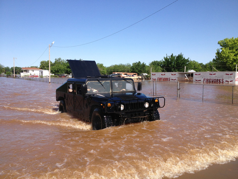 Photo - An Oklahoma County Sheriffs Dept. Humvee brings out residents from a flooded mobile home park off of air depot between 10th & 23rd. Photo by Paul Hellstern
