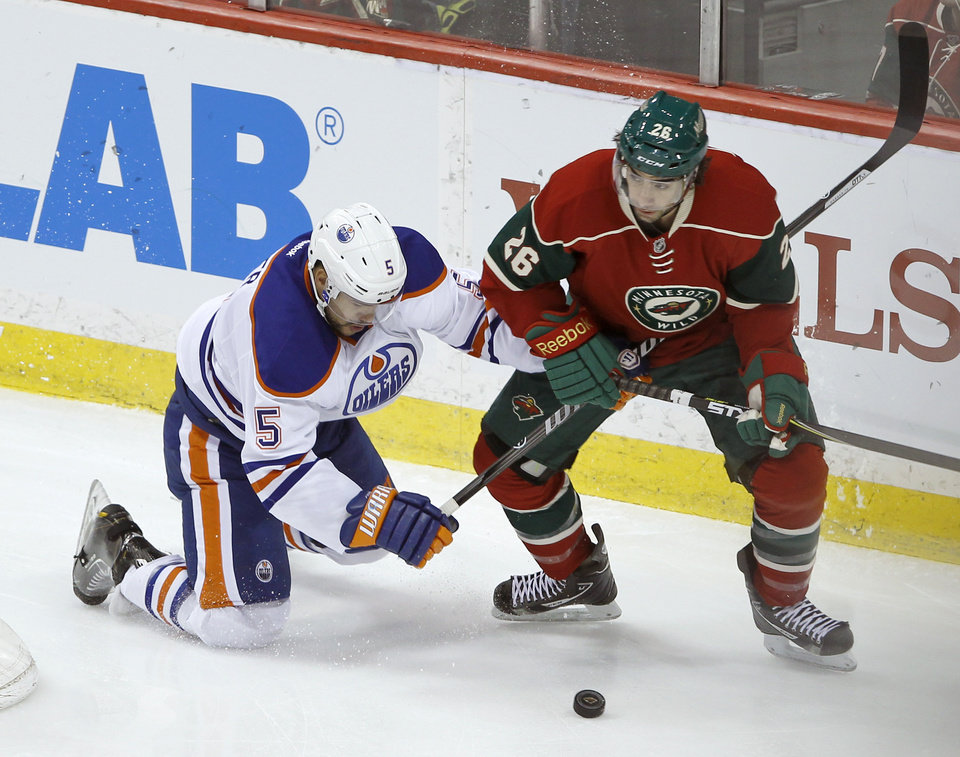 Photo - Edmonton Oilers defenseman Mark Fraser (5) and Minnesota Wild left wing Matt Moulson (26) tangle as they chase the puck during the first period of an NHL hockey game in St. Paul, Minn., Tuesday, March 11, 2014. (AP Photo/Ann Heisenfelt)