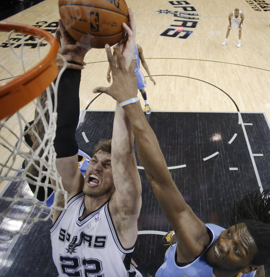 San Antonio Spurs' Tiago Splitter, left, of Brazil, is impeded by Denver Nugget defenders Wilson Chandler, left, and Kenneth Faried, right, as he tries to score during the second half of an NBA basketball game, Wednesday, March 27, 2013, in San Antonio. San Antonio won 100-99. (AP Photo/Eric Gay)