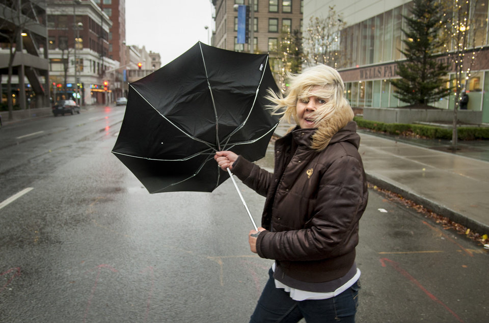 Photo -   During a strong gust of wind, Michele Purkey's umbrella flips back as she crosses the intersection of First Avenue and Wall Street on Monday, Nov. 19, 2012, in downtown Spokane, Wash. Residents in Washington and Oregon are bracing for expected river flooding after heavy rain and winds that caused sporadic road closures, power outages and at least one death. The wet weather is expected to continue throughout the week, after hurricane-strength winds battered both states along the coast. (AP Photo/The Spokesman-Review, Colin Mulvany)