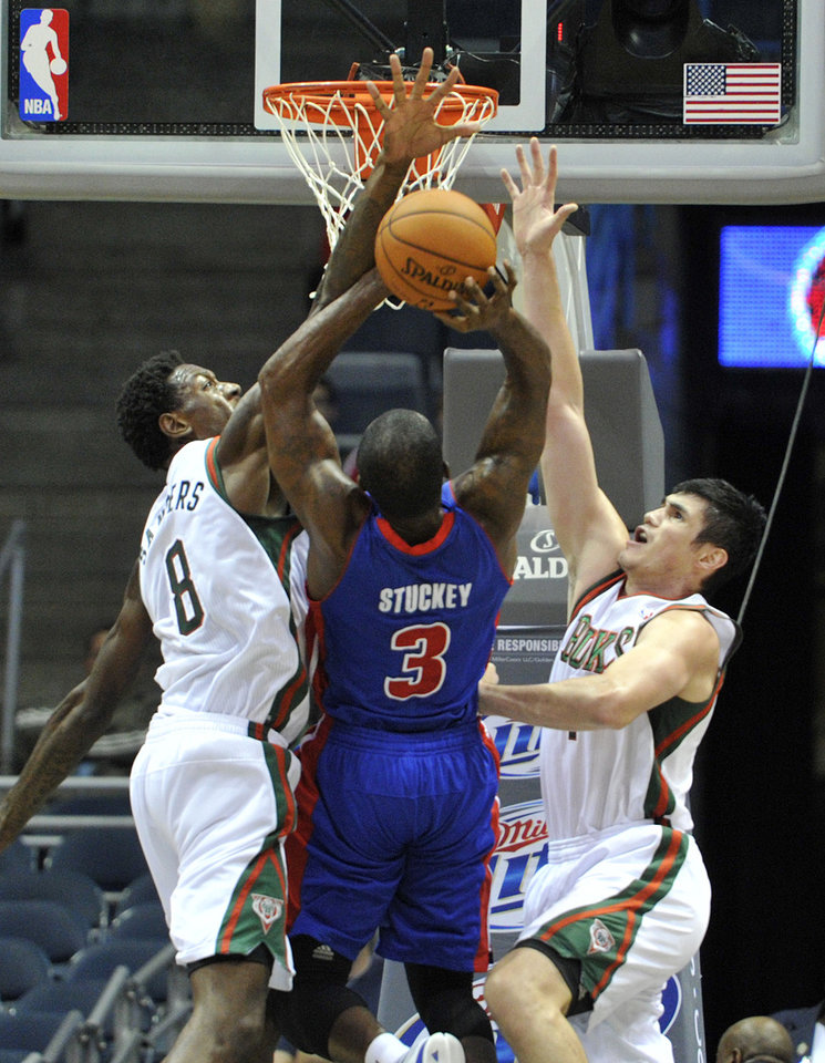 Milwaukee Bucks' Larry Sanders (8) and Ersan Ilyasova block the shot of Detroit Pistons' Rodney Stuckey (3) during the second half of an NBA basketball game on Saturday, Oct. 13, 2012, in Milwaukee. The Bucks defeated the Pistons 108-91. (AP Photo/Jim Prisching)