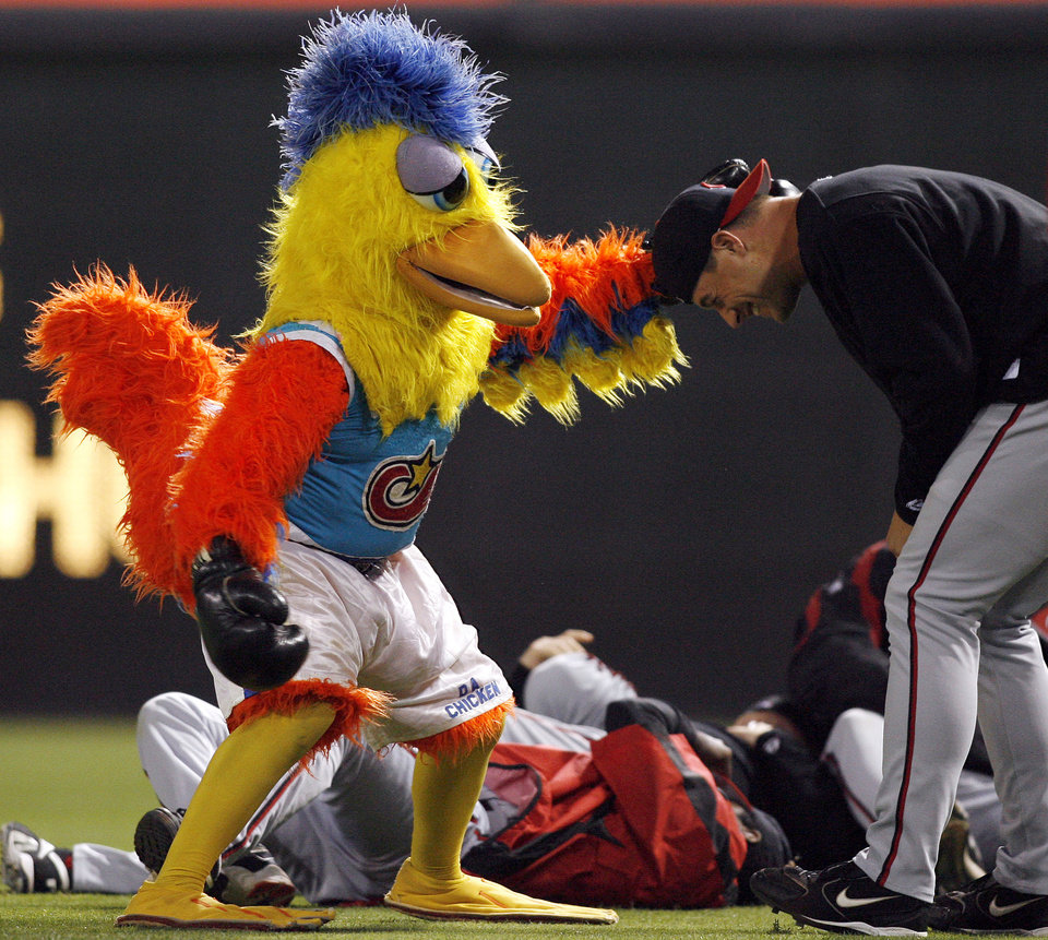 Photo - MASCOT: The Famous Chicken, left, has a mock fight with Cincinnati Reds pitcher Jason Standridge, right, in the bullpen during the fourth inning of a major league baseball game between the Reds and the San Diego Padres on Saturday, Sept. 2, 2006, in San Diego. (AP Photo/Denis Poroy) ORG XMIT: CADP106 ORG XMIT: 0806211936285984