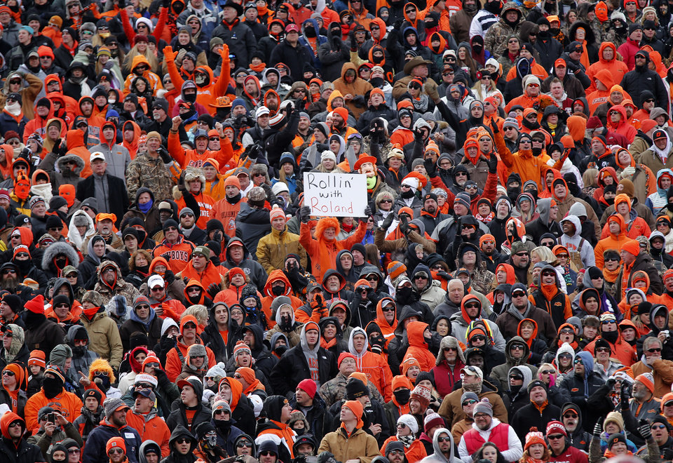 Photo - A Cowboys' fan cheers on the team during the Bedlam college football game between the Oklahoma State University Cowboys (OSU) and the University of Oklahoma Sooners (OU) at Boone Pickens Stadium in Stillwater, Okla., Saturday, Dec. 7, 2013. Photo by Chris Landsberger, The Oklahoman