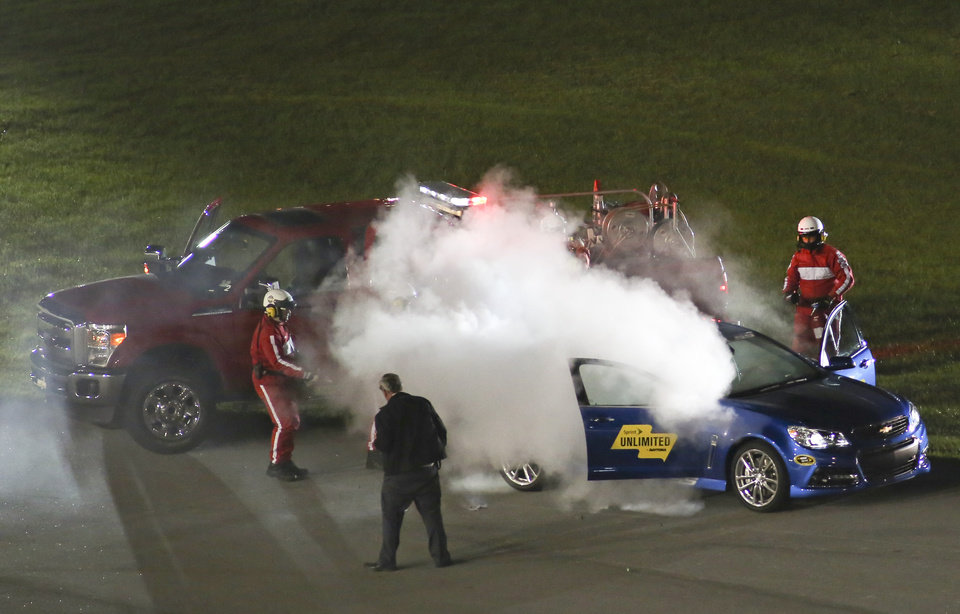 Photo - Track workers extinguish a fire that started in the pace car during the NASCAR Sprint Unlimited auto race at Daytona International Speedway in Daytona Beach, Fla., Saturday, Feb. 15, 2014. (AP Photo/Jim Topper)