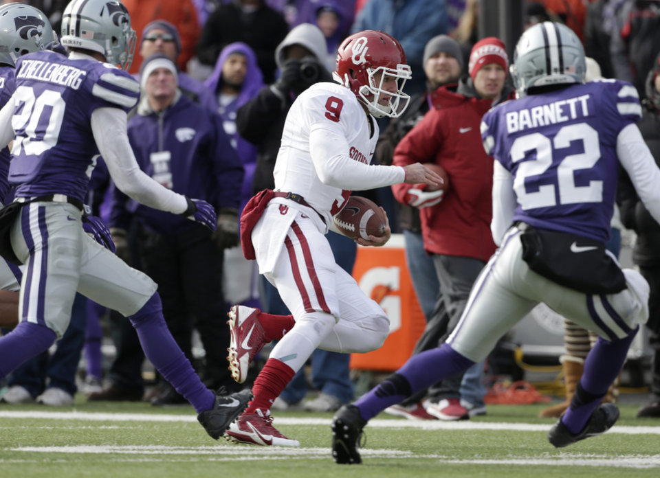 Oklahoma quarterback Trevor Knight (9) gets past Kansas State defensive backs Dylan Schellenberg (20) and Dante Barnett (22) to get a first down during the first half of an NCAA college football game Saturday, Nov. 23, 2013 in Manhattan, Kan. (AP Photo/Charlie Riedel)