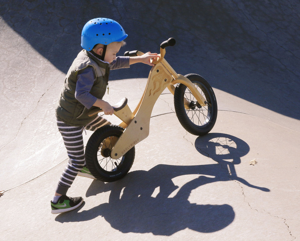 Photo -  Hank Scovel, 3, pushes his bike over the hump at the Mathis Brothers Skate Park. [PHOTO BY PAUL HELLSTERN, THE OKLAHOMAN]