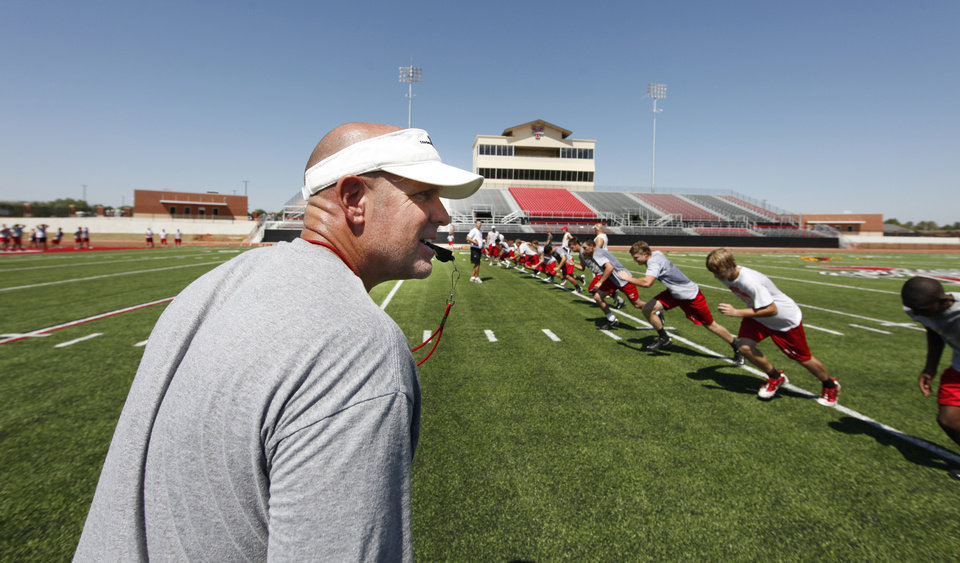 Photo - Coach Todd Wilson leads drills during practice in the new stadium in Yukon, Tuesday, August 08, 2011. Photo by Steve Gooch
