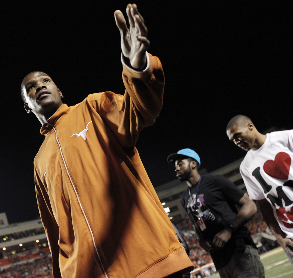 Photo - From left, Kevin Durant, James Harden and Russell Westbrook of the Oklahoma City Thuder walk the sidelines during the college football game between the Oklahoma State University Cowboys (OSU) and the University of Texas Longhorns (UT) at Boone Pickens Stadium in Stillwater, Okla., Saturday, Oct. 31, 2009. Texas won, 41-14. Photo by Nate Billings, The Oklahoman
