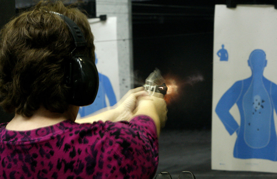 Peggy Osterholt, of Okarche, fires her handgun inside H&H Shooting Sports Complex in Oklahoma City. Photo by Bryan Terry, The Oklahoman