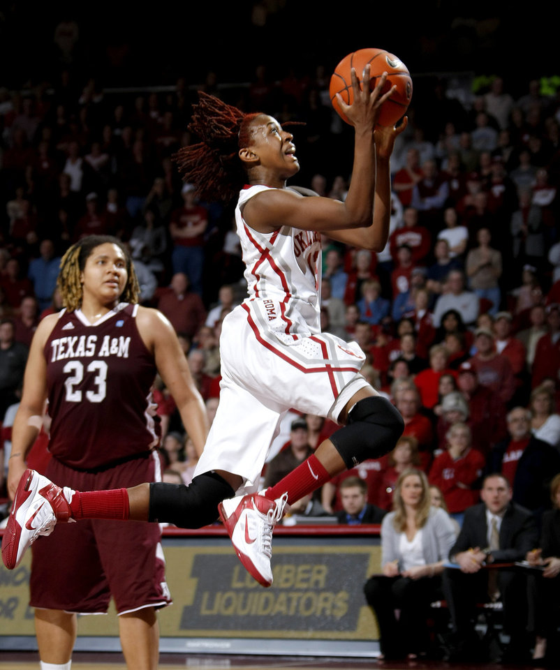 Photo - OU's Danielle Robinson (13) lepas past Texas A&M's Danielle Adams (23) during the Big 12 women's basketball game between the University of Oklahoma and Texas A&M at Lloyd Noble Center in Norman, Okla., Wednesday January 26, 2011.  Photo by Bryan Terry, The Oklahoman
