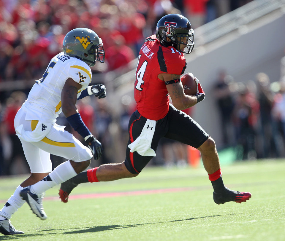 Photo -   Texas Tech's Darrin Moore gets away from West Virginia's Pat Miller during an NCAA college football game in Lubbock, Texas, Saturday, Oct. 13, 2012. (AP Photo/Lubbock Avalanche-Journal, Stephen Spillman) LOCAL TV OUT