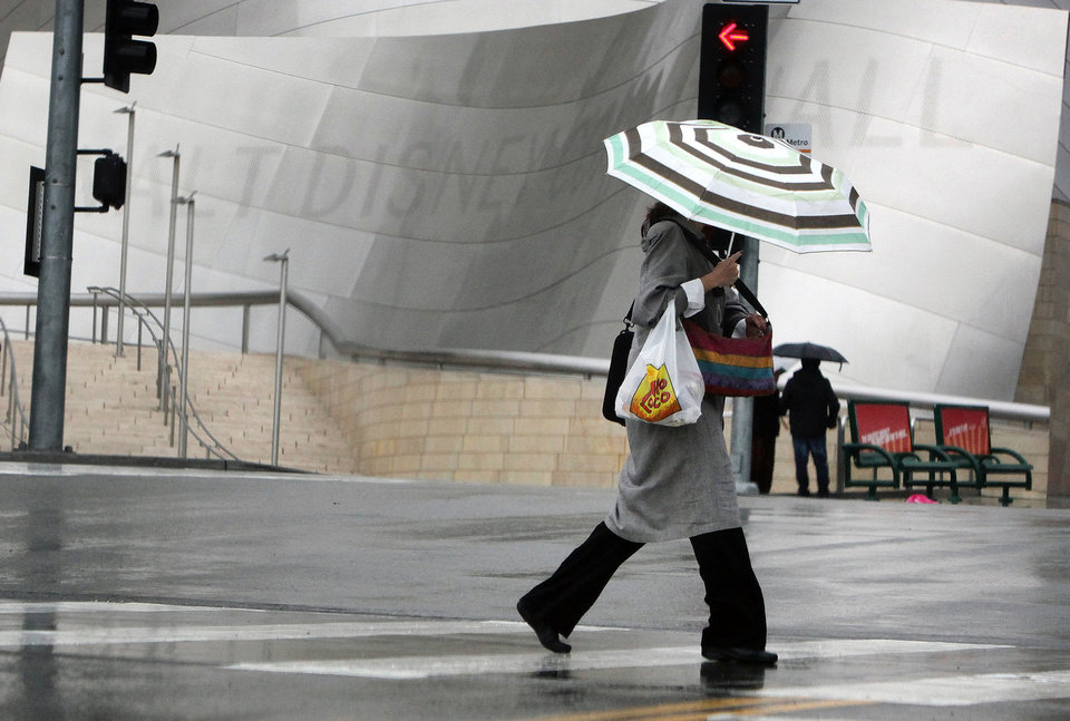 Photo - A pedestrian covers from the rain as she makes her way past the Disney Music Center in downtown Los Angeles on Friday, Feb. 28, 2014. The first wave of a powerful Pacific storm spread rain and snow early Friday through much of California, where communities endangered by a wildfire just weeks ago now faced the threat of mud and debris flows.(AP Photo/Richard Vogel)