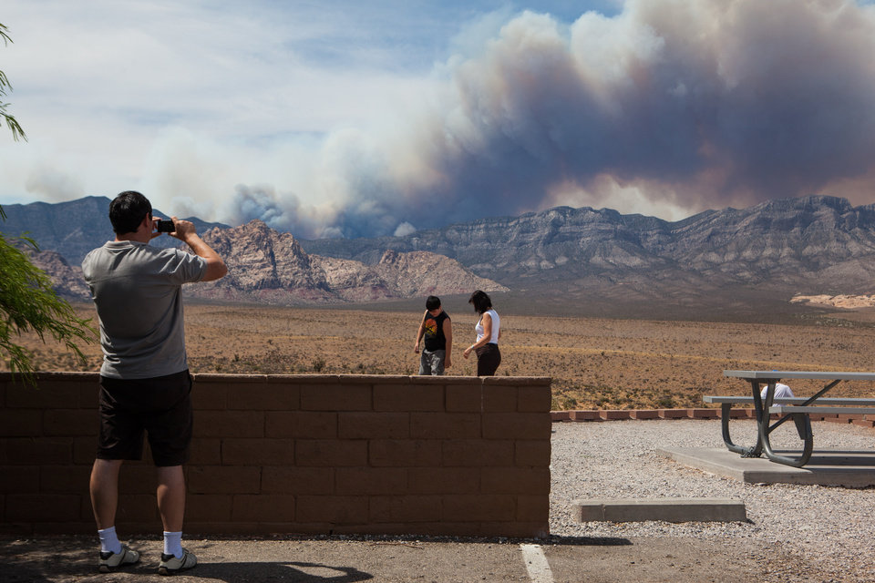 Photo - A family visiting the Red Rock Canyon National Conservation Area takes photos as smoke from the Carpenter 1 fire rises over Mount Charleston near Las Vegas on Tuesday, July 9, 2013. The fire which started by lightning-strike on July 1 is only fifteen percent contained. (AP Photo/Las Vegas Review-Journal, Chase Stevens)